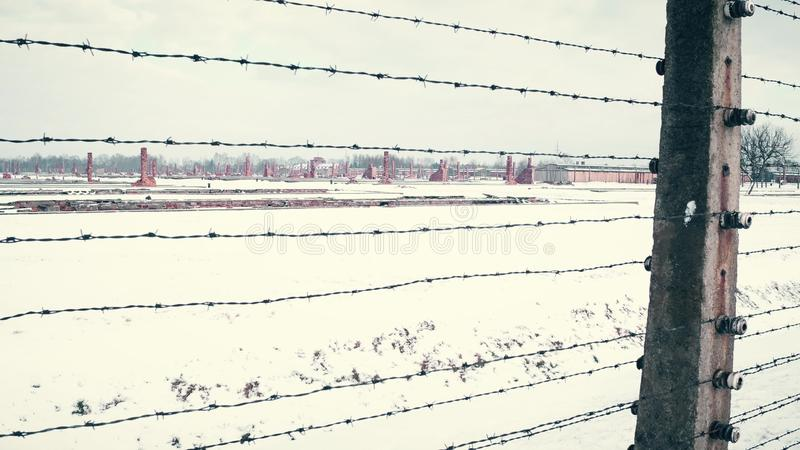 Old rusty barbed wire fence and distant ruined barracks of concentration camp in the snow. 4K steadicam shot royalty free stock images