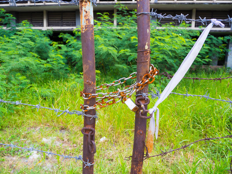 Old rusty barbed wire fence locked by master key chain royalty free stock photo