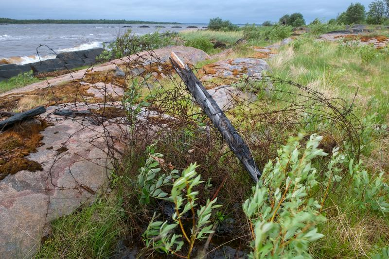Concentration camp fence. Old rusty barbed wire at the site of an SLON concentration camp on the shore of the White Sea in stormy weather royalty free stock photo