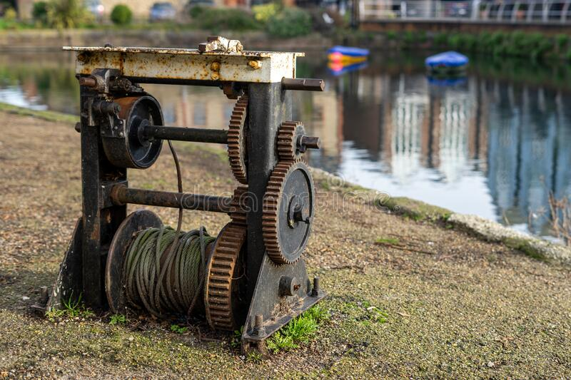An old rusty Barge winch next to a canal used as part of an old canal lock stock images