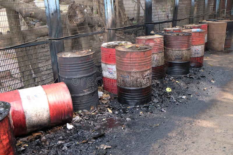 Old rusty barrel left in the road leaking thick black tar or oil on an urban street in Kolkata royalty free stock images