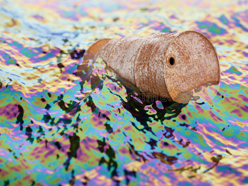 Old rusty barrel in polluted water with oil film royalty free stock photo
