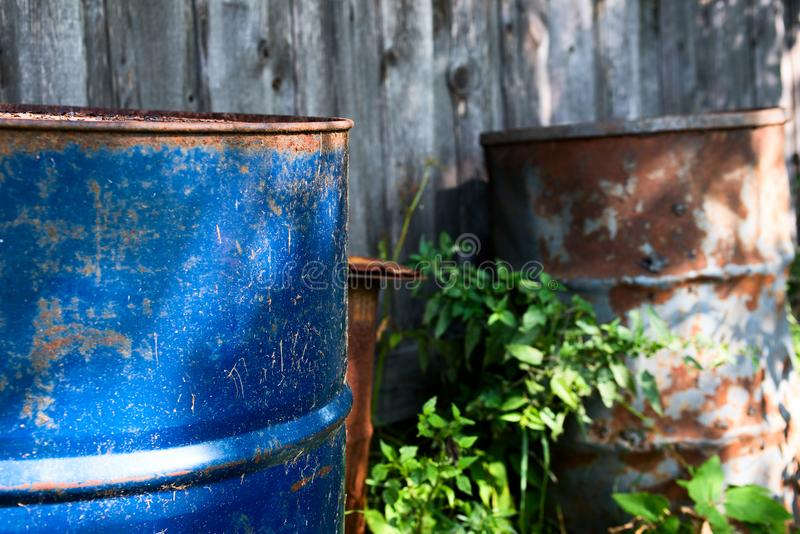 Old rusty barrels near a wooden fence. Is close royalty free stock images