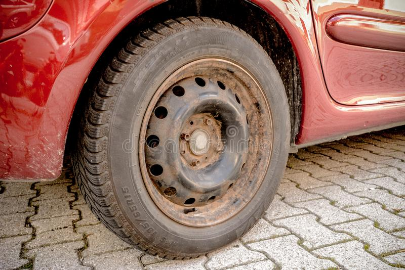 Old rusty car wheel disc. Old rusty black car disc on a red car stock photography