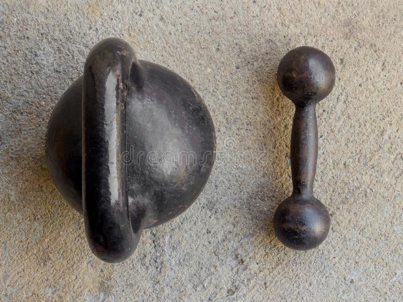 Old rusty black kettlebell and small dumbbell on noncrete floor. Background top view royalty free stock image