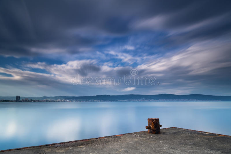 Old rusty bollard on the quay royalty free stock photography