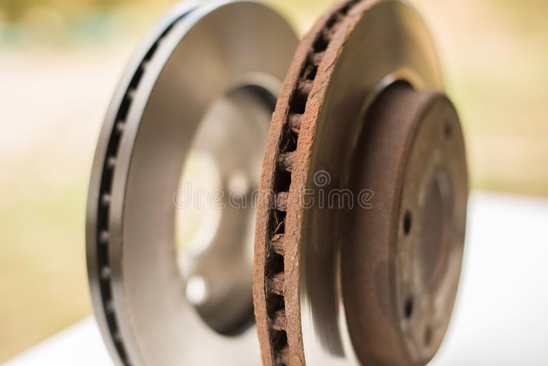Old rusty brake disc and new disc in the background. Selective focus stock photos