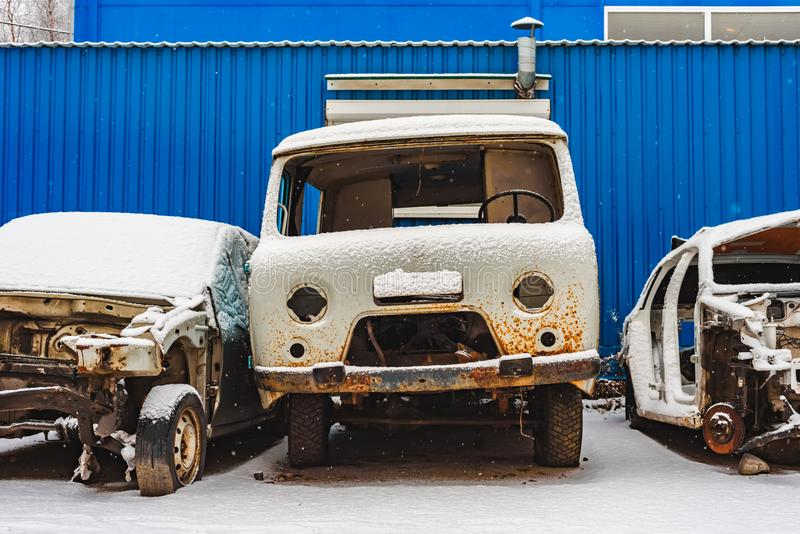 The old rusty broken cars on a dump. Under snow royalty free stock photos