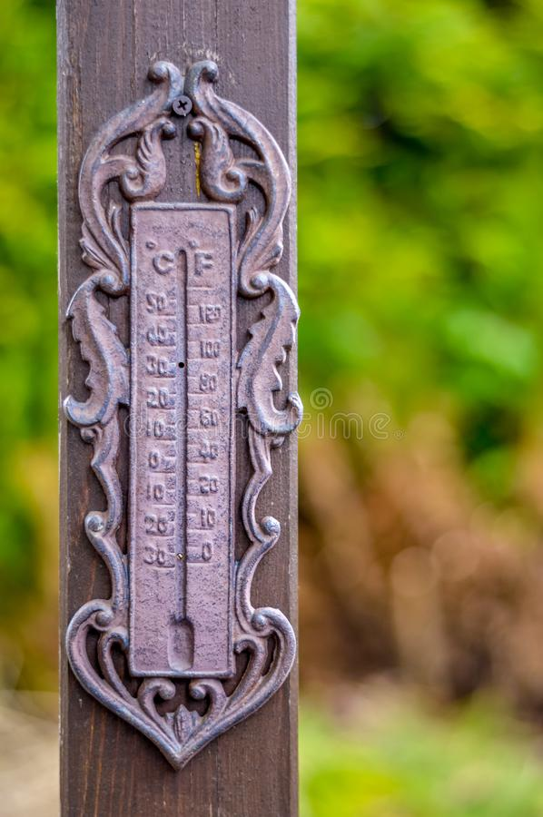 Old rusty broken thermometer on a wooden pole. An old rusty thermometer hanging on a brown wooden pole royalty free stock images