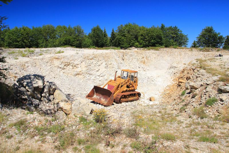 Old rusty bulldozer in abandoned stone pit. Green forest and blue sky in background royalty free stock photography