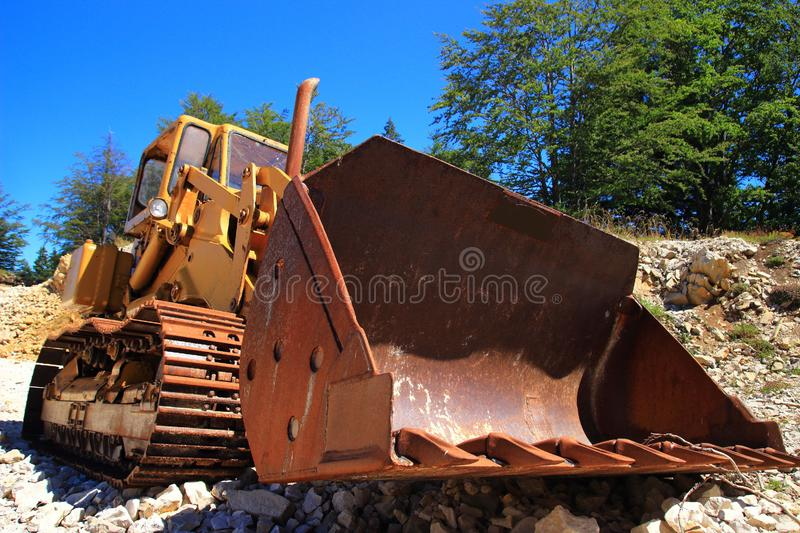 Old rusty bulldozer in abandoned stone pit. Green forest and blue sky in background royalty free stock photo