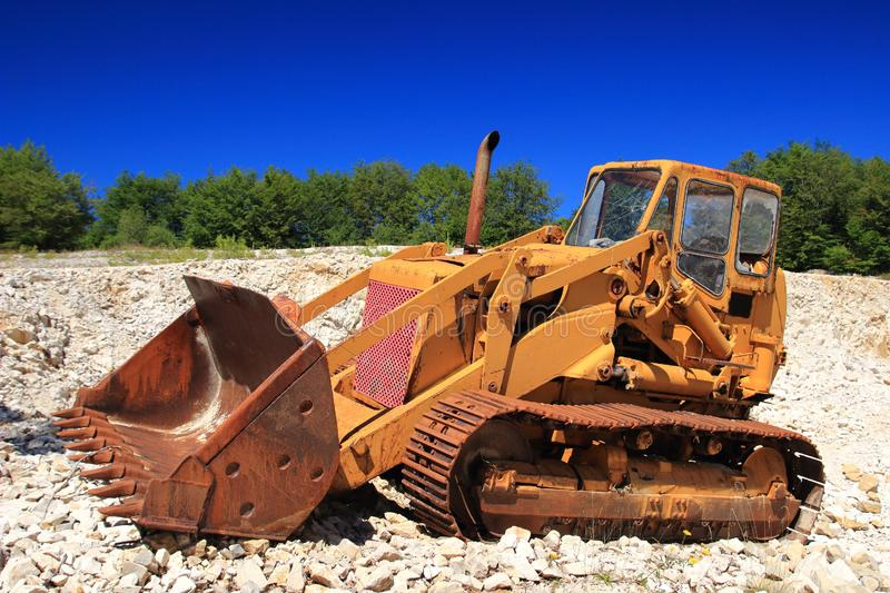 Old rusty bulldozer in abandoned stone pit. Green forest and blue sky in background stock images