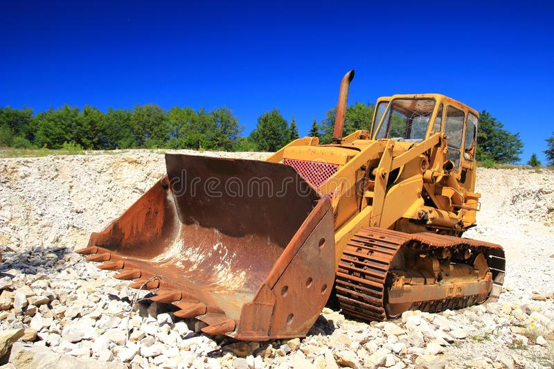 Old rusty bulldozer in abandoned stone pit. Green forest and blue sky in background stock image