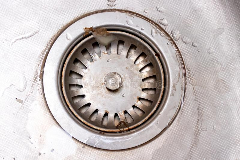 Old rusty calcified drain hole in the kitchen sink with limescale and scurf scum.  royalty free stock photo