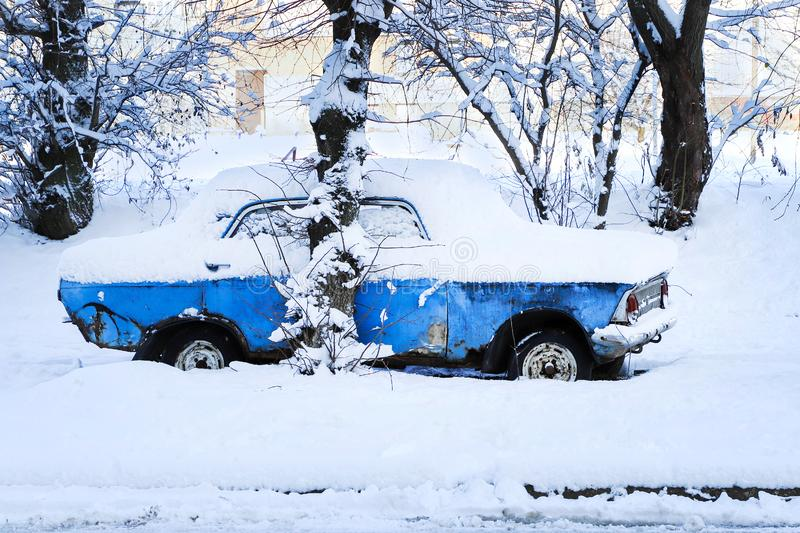 Old rusty car covered in snow.  stock image