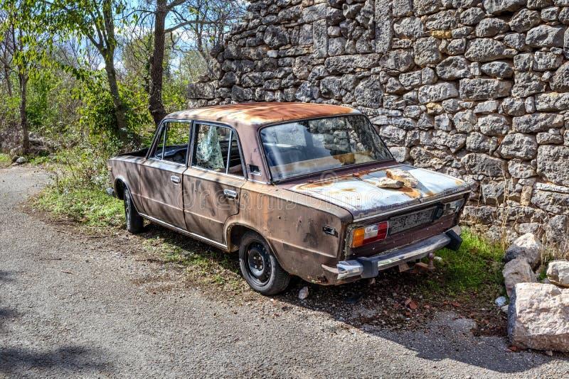 Old rusty car in croatian village. stock photos