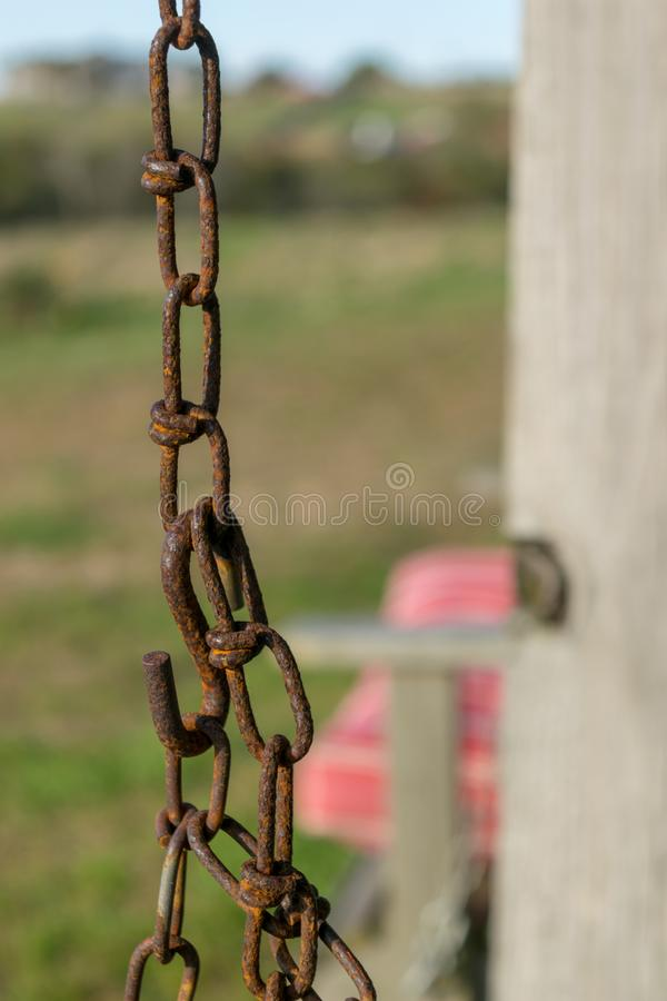 Old rusty chain and chain links, against a bokeh landscape, with a wooden pole and pink seat in the background, Block. Old rusty chain and chain links against a stock images