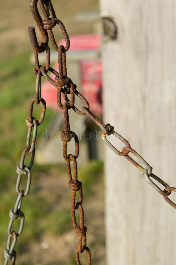 Old rusty chain and chain links, against a bokeh wooden pole and pink seat in the background, Block Island, RI royalty free stock photography
