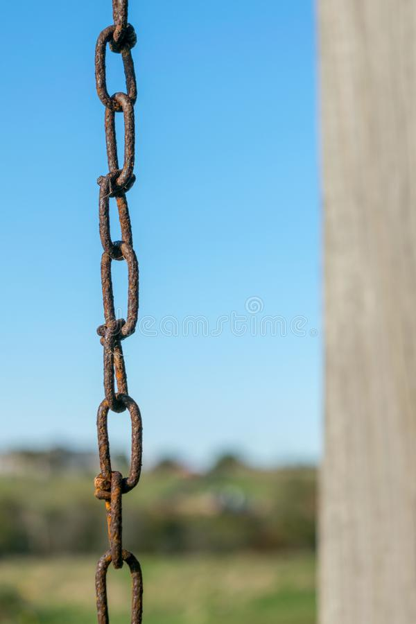 Old rusty chain and chain links, against a natural blue sky and green landscape bokeh background, Block Island, RI stock photo