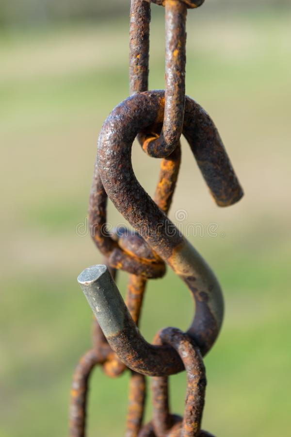 Old rusty chain, chain links, and large s-hook, with a green bokeh background, close-up, Block Island, RI royalty free stock photos