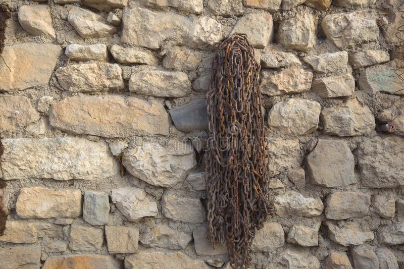 Old rusty chain hanging on the wall of a village house. Texture stock photography