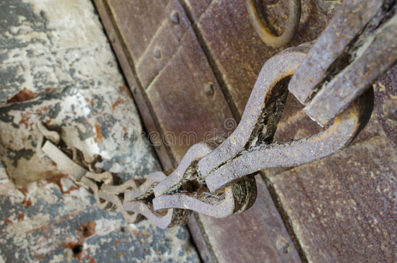 Old rusty chain and massive doors. Old rusty chain and massive wrought iron doors stock image