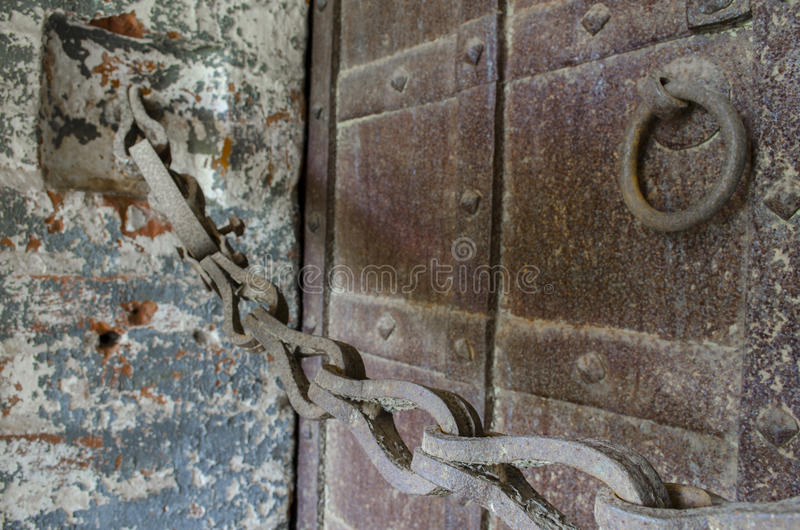 Old rusty chain and massive doors. Old rusty chain and massive wrought iron doors royalty free stock photos