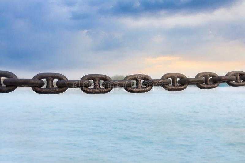 The old rusty chain on sea background. Chain refers to a set of flexible connectors connecting the metal used for seizure or confiscation of objects and draw stock photo