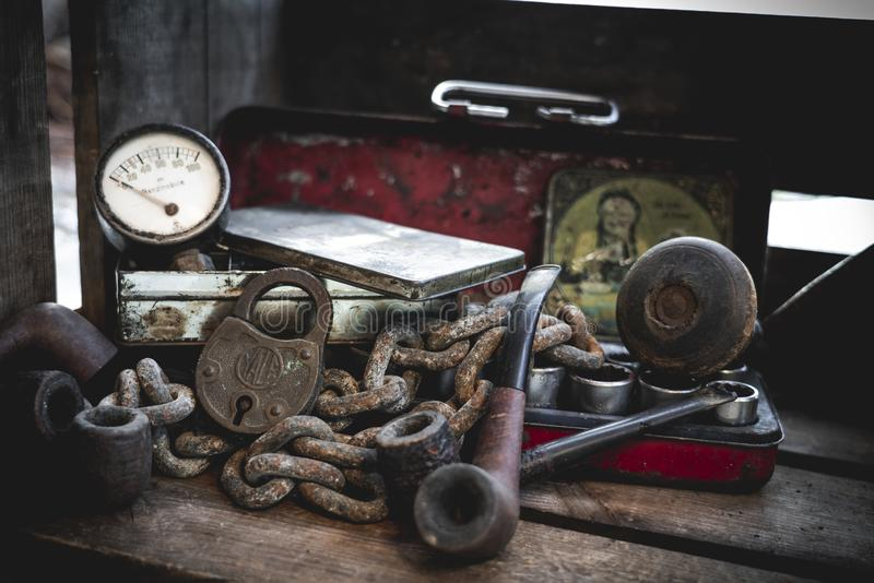 Old rusty chain, tobacco pipes, antique red box and old gauge valve stock image