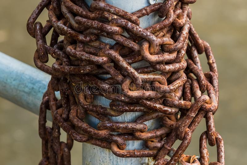 Old rusty chains on a steel pole. Metal, iron, texture, close, closeup, grunge, vintage, fence, background, brown, equipment, outdoor, safety, design, security stock image