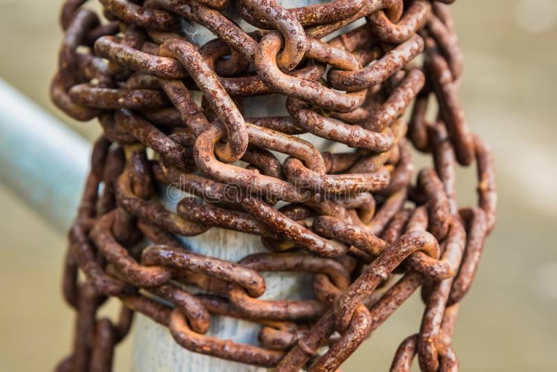 Old rusty chains on a steel pole. Metal, iron, texture, close, closeup, grunge, vintage, fence, background, brown, equipment, outdoor, safety, design, security royalty free stock image