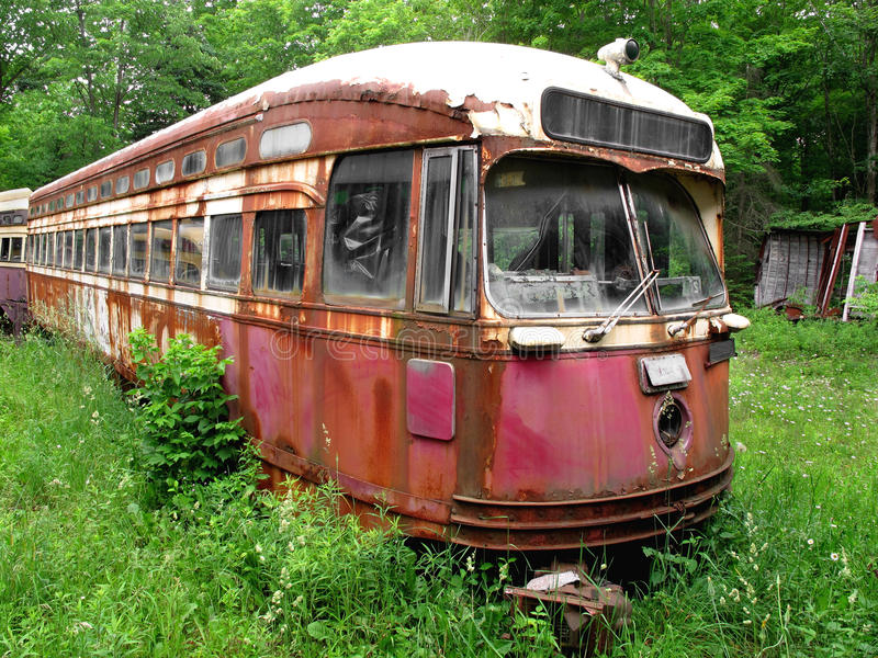 Old And Rusty City Streetcar In Trees Royalty Free Stock Image