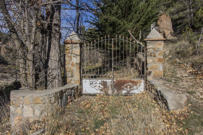 Old rusty closed iron gate at the entrance to the garden royalty free stock image