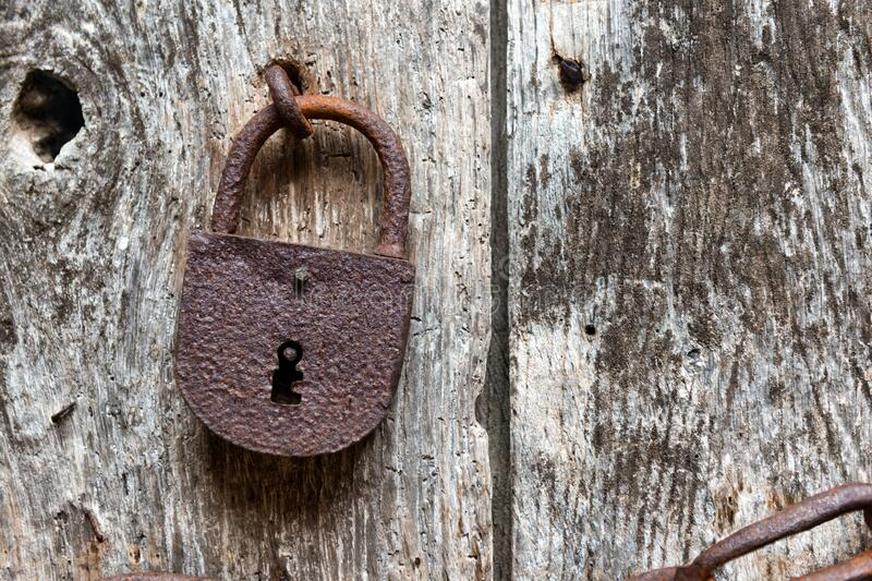 Old rusty closed lock. On an ancient wooden door stock photography