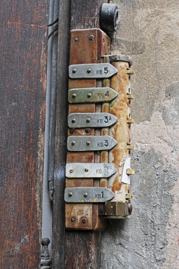 Old rusty door bells with buttons and tables royalty free stock image