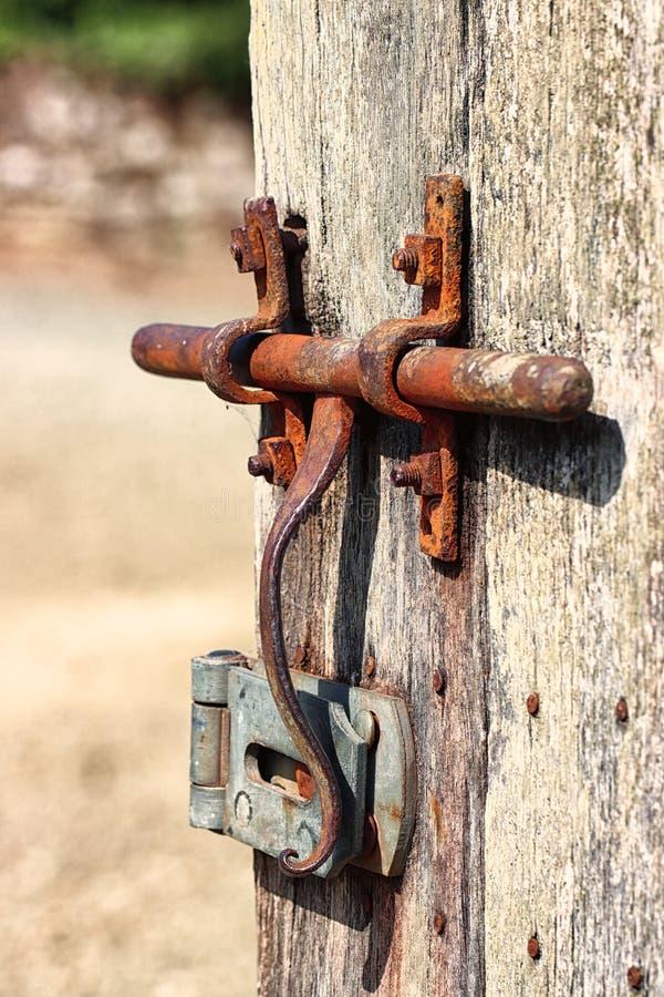 Old rusty door bolt on a rustic door stock photos