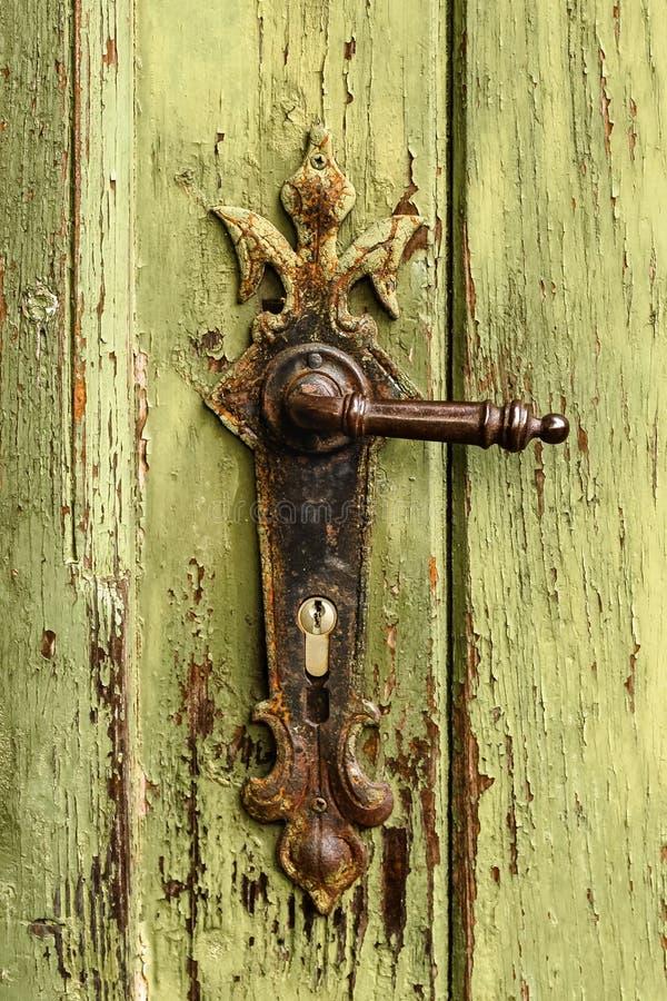 Old rusty door handle on green door. Detail of rustic old vintage and rusty grungy iron door handle installed on an ornament door stock photography