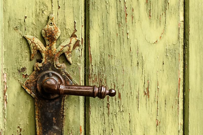Old rusty door handle on green door. Detail of rustic old vintage and rusty grungy iron door handle installed on an ornamented old royalty free stock photography