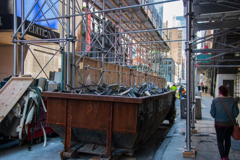 Old rusty dumpster on a city street construction site royalty free stock photography