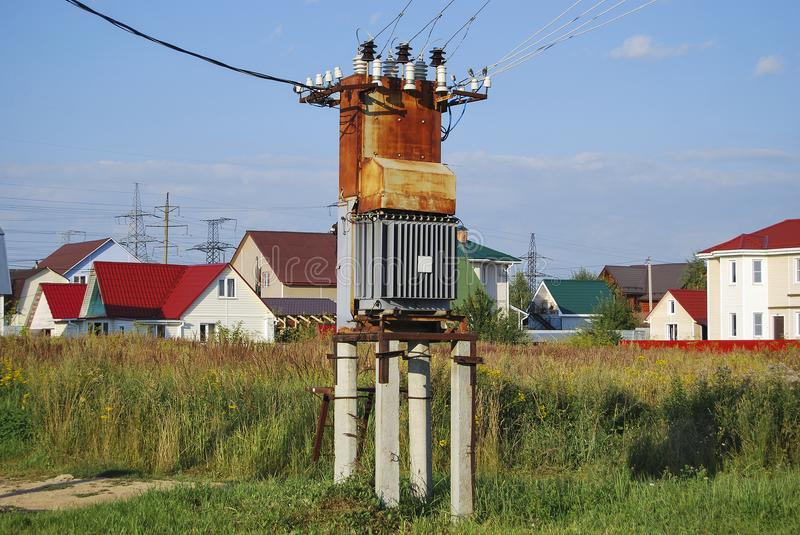 Old rusty electrical distribution transformer. With cooling fins in the village. Against the backdrop of village houses royalty free stock images