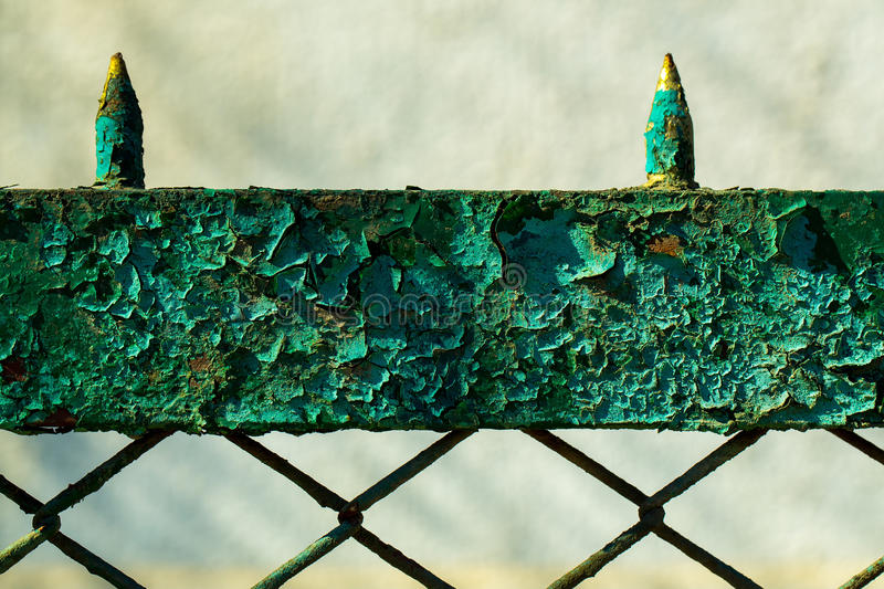 Old rusty fence. Old fence rusty forged metallized with peeled green paint on sunny day on grey background royalty free stock photos