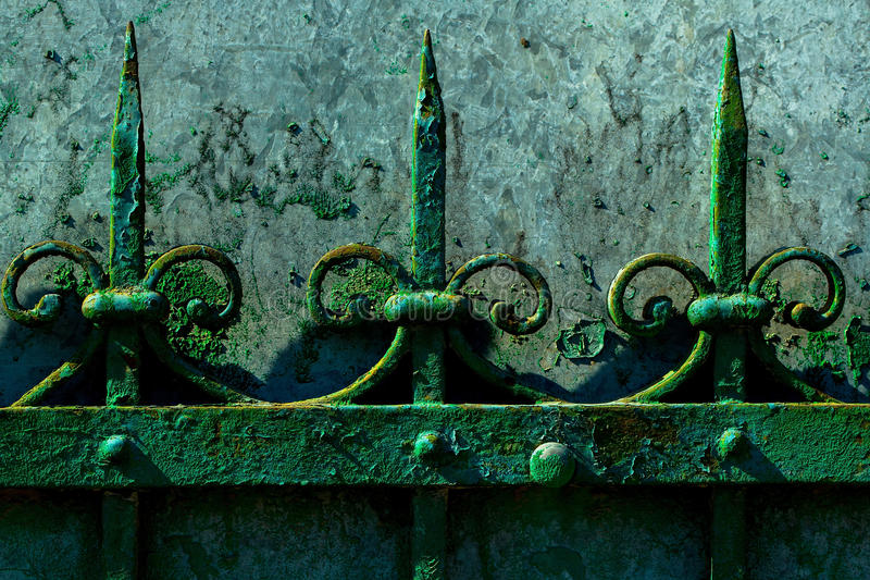Old rusty fence. Old fence rusty forged metallized with peeled green paint on sunny day on grey wall background stock image