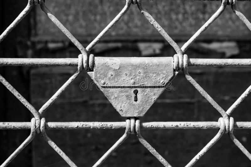 Old rusty fence with keyhole. In black and white royalty free stock images
