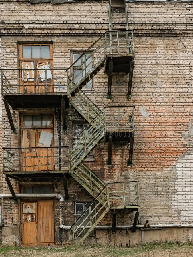 Old rusty fire escape on an abandoned industrial building stock photo