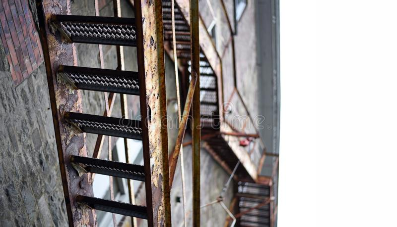 Vintage fire escape stairs on brick building from below stock photo