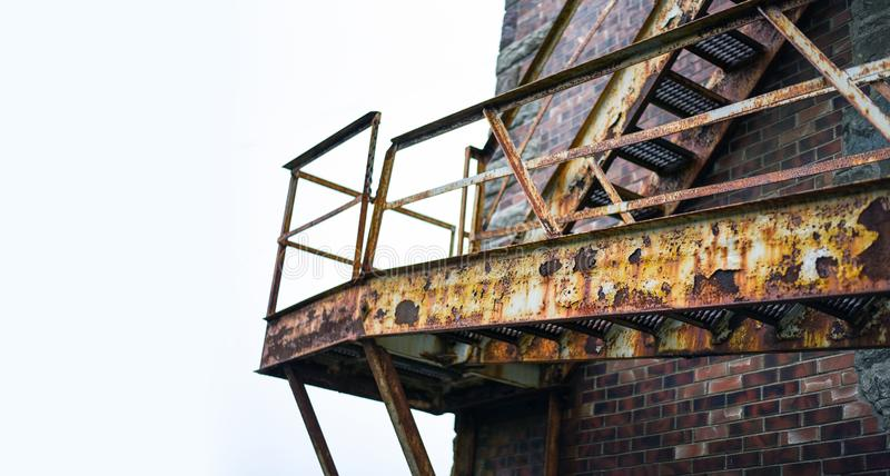 Vintage fire escape stairs on brick building from below royalty free stock photo