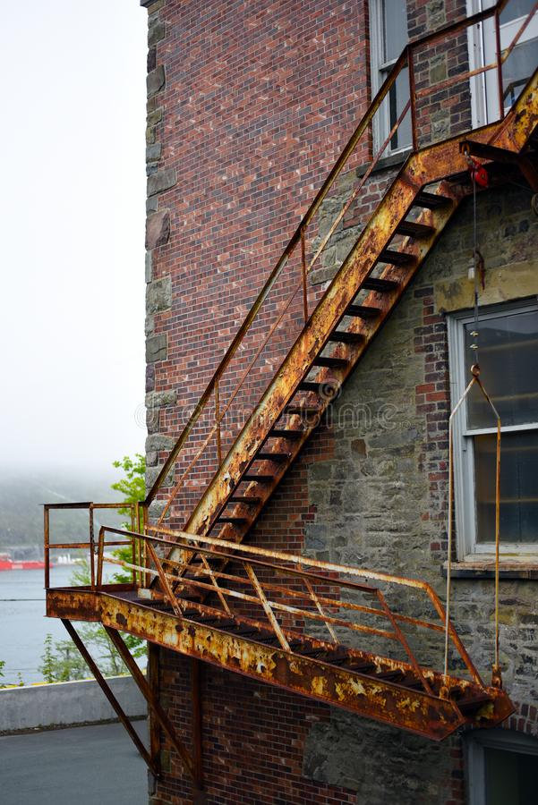 Rusty fire escape stairs on brick building stock images