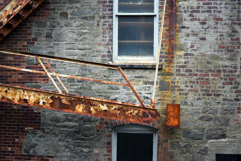 Vintage fire escape stairs with heavy weight on brick building royalty free stock photos