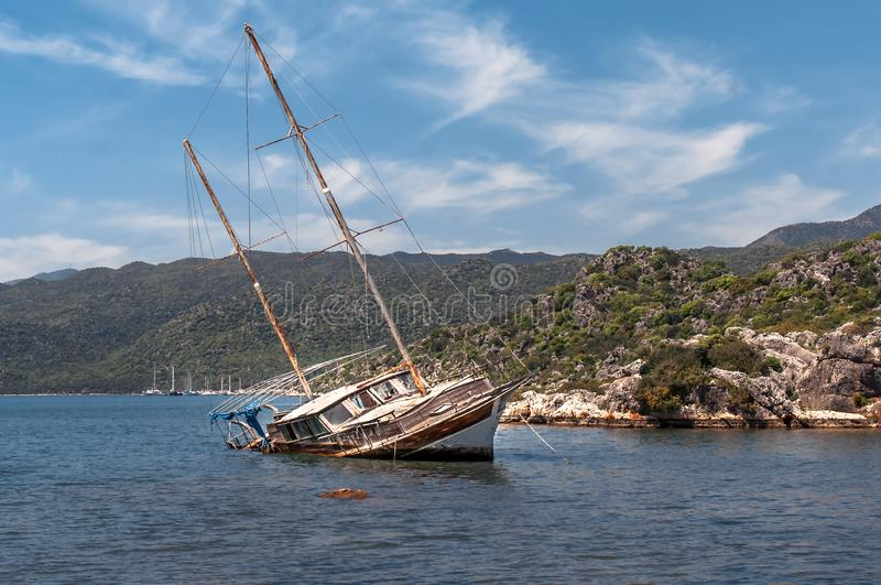 Old rusty flooded sailboat stranded on a reef in the sea, shipwreck, turkey stock image