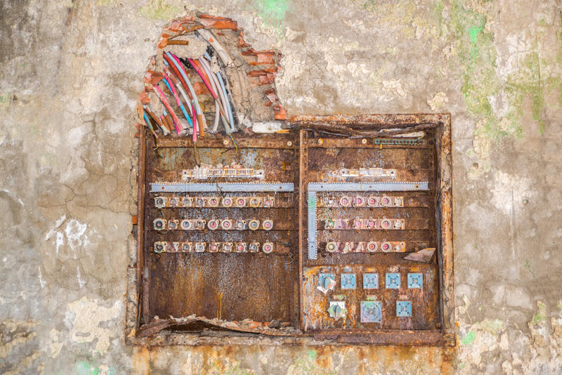 Old rusty fuse box. With broken dangerous wires above stock photo
